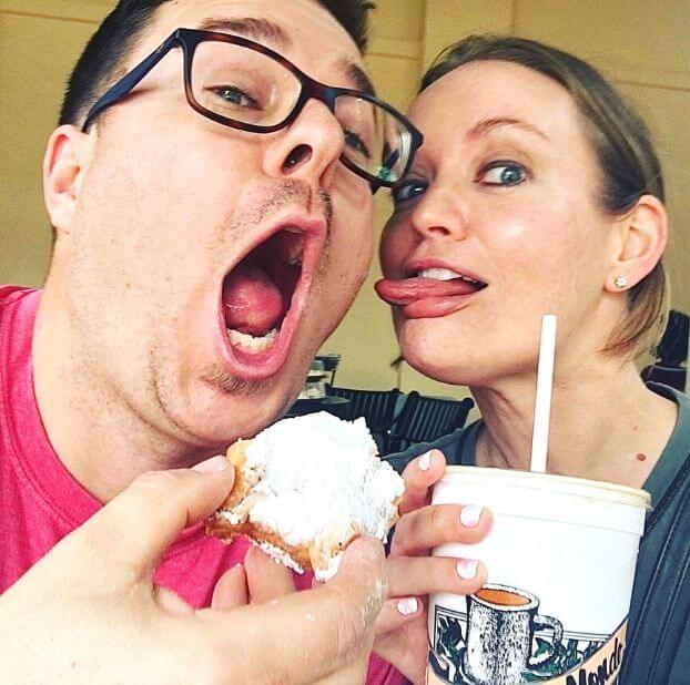 man and woman making silly faces while eating powdered doughnut