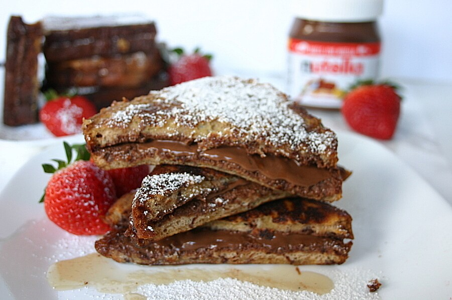french toast with nutella stacked on a plate with powdered sugar on top
