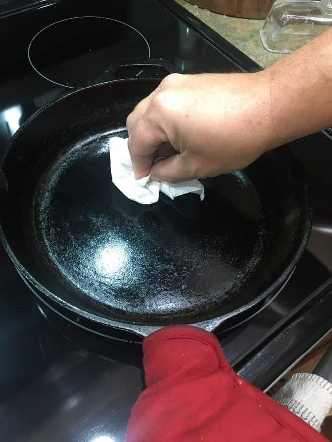 man's hand showing how to season a cast iron skillet