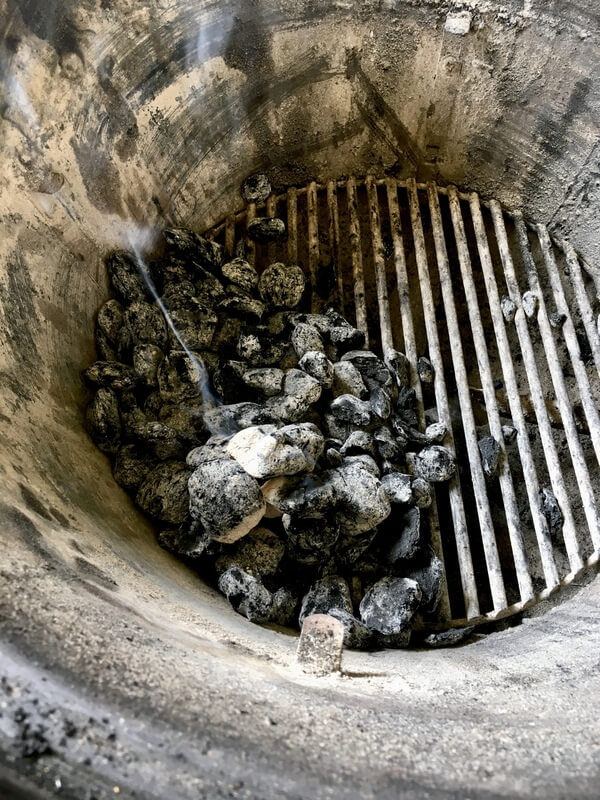 charcoal briquettes on one side of a kettle grill