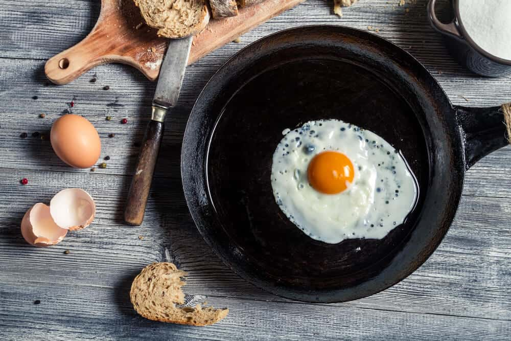 over easy egg cooking in a cast iron skillet