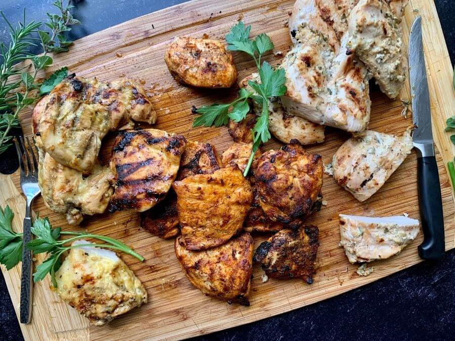 charcoal grilled chicken breasts on a cutting board