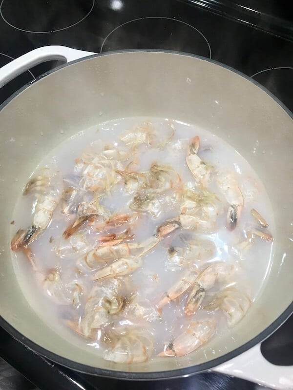 chicken broth and shrimp shells boiling in a dutch oven