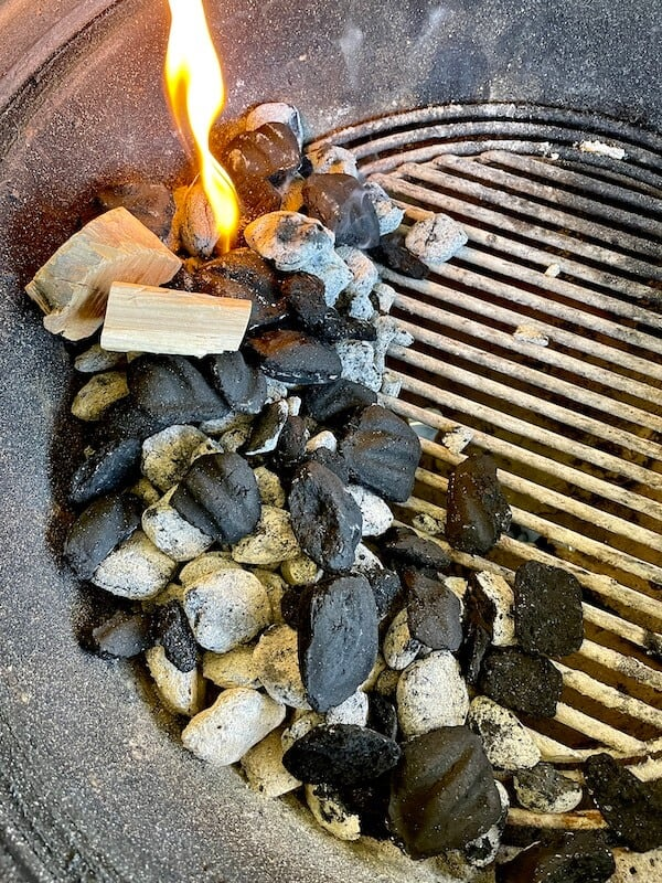 charcoal and wood chunks smoking in a charcoal grill