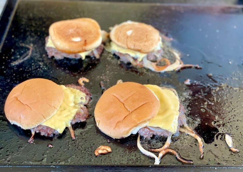 onion burgers on flat top grill with hamburger buns steaming