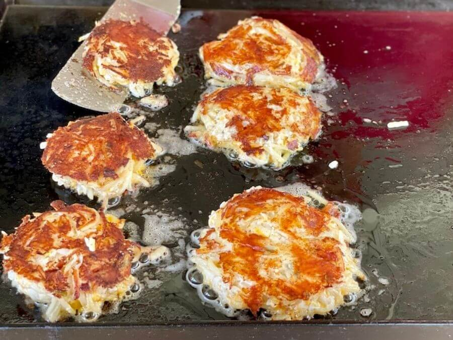 hashbrown casserole cooking on a flat top grill