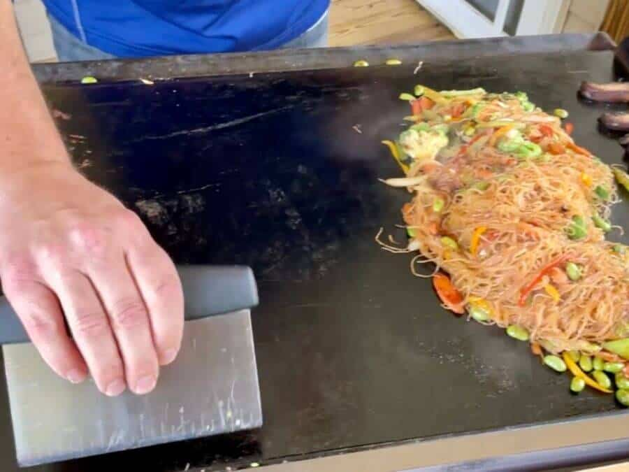 using a bench scraper on a flat top griddle