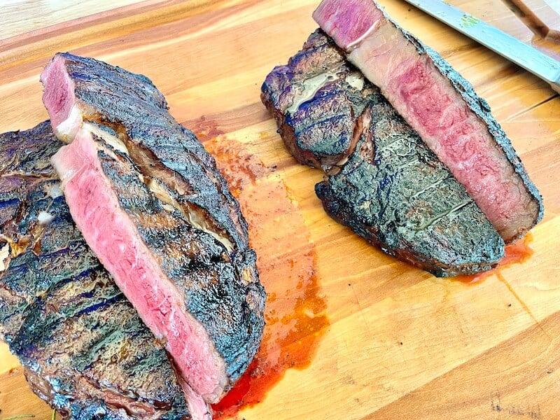 grilled ribeyes cut open on a cutting board