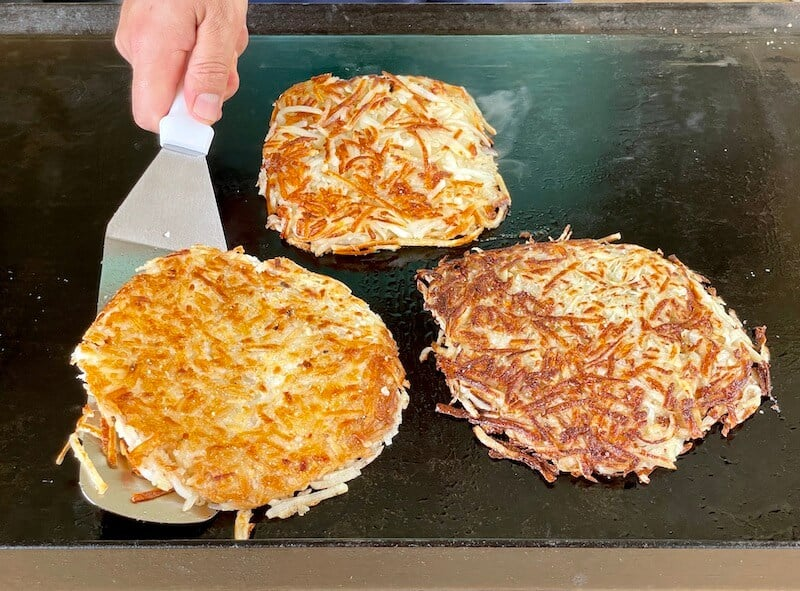 cooking hash browns on a flat top grill